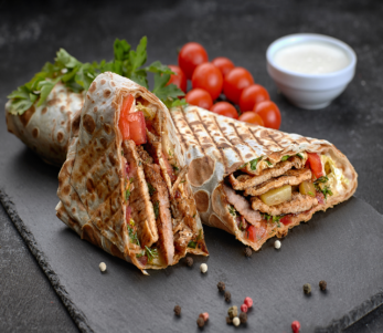2 pork-shawarma-black-background-with-herbs-tomatoes-sauce